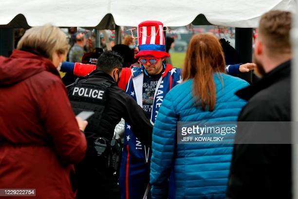 """Supporter goes through security before US Vice President Mike Pence speaks at a """"Make America Great Again!"""" campaign event at Oakland County..."""