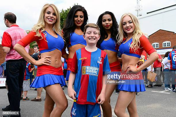A supporter has his picture taken with the Crystal girls ahead of the Premier League match between Crystal Palace FC and West Bromwich Albion FC at...