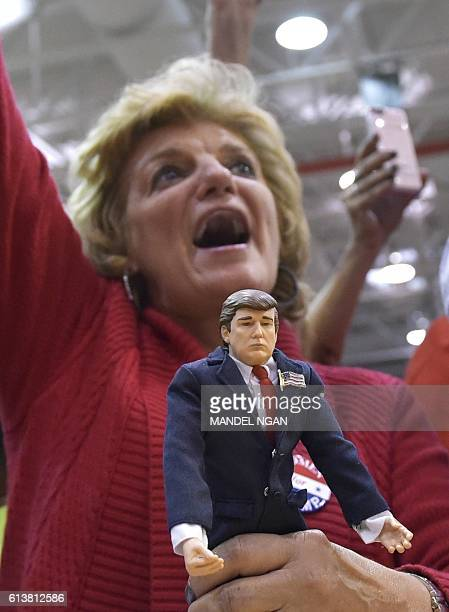 A supporter holding a Trump doll cheers as Republican presidential nominee Donald Trump speaks during a rally at Ambridge Area Senior High School on...