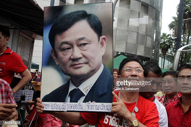 Supporter holding up a portrait of ousted Thai prime minister Thaksin Shinawatra during a rally in Ratchaprasong junction. Red-shirts protesters mark...