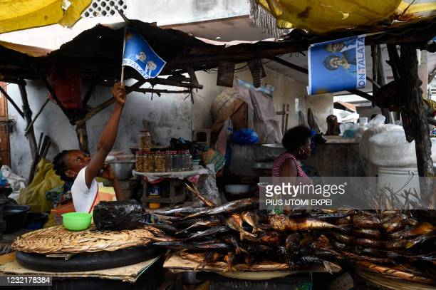 Supporter holds a campaign flag with photographs of incumbent Benin President Patrice Talon and running mate Mariam Talata at the market in Cotonou...