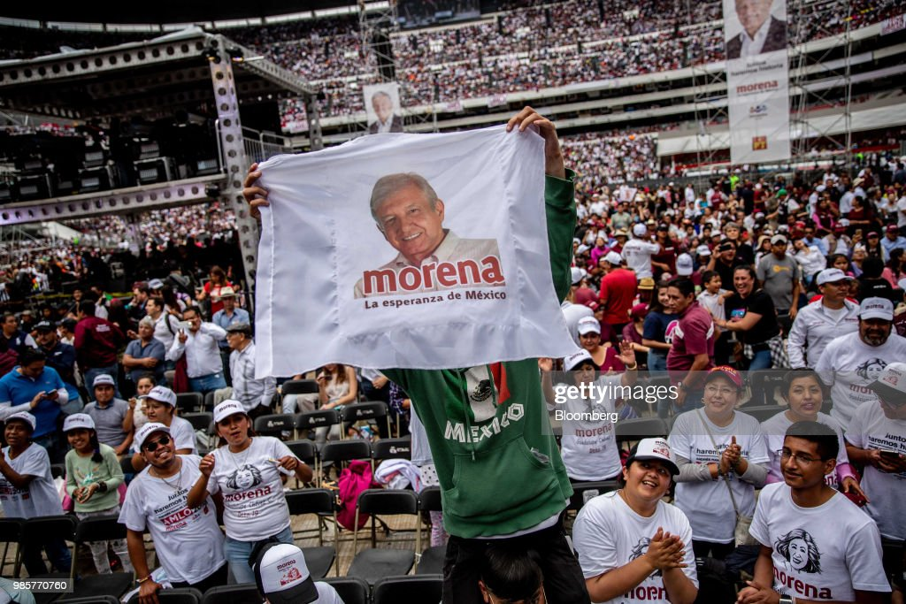 A supporter holds a flag featuring a portrait of Andres Manuel Lopez Obrador, presidential candidate of the National Regeneration Movement Party (MORENA), during the final campaign rally at the Estadio Azteca in Mexico City, Mexico, on Wednesday, June 27, 2018. Lopez Obrador promises to put the poor first with a raft of new social programs -- and to stand up to the U.S. President, who has been denouncing Mexico since before he got elected. Photographer: Alejandro Cegarra/Bloomberg via Getty Images