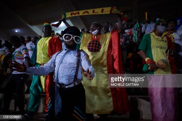 Supporter holds a flag of the Malian football team during the projection of the final match of the African Nations Championship between Mali and...
