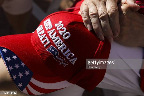 """Supporter holds a hat that reads """"2020 Keep America Great!"""" while standing in line to enter an executive order signing event with U.S. President..."""