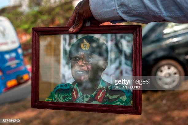 A supporter holds a portrait of Zimbabwe's Defence Force chief Constantino Chiwenga as supporters gather to welcome Zimbabwe's ousted vice president...