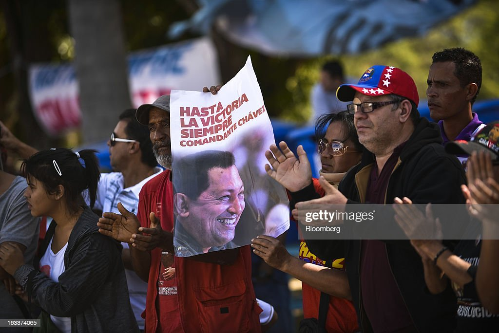 A supporter holds a poster as others applaud during the funeral for Venezuelan President Hugo Chavez in Caracas, Venezuela, on Friday, March 8, 2013. Allies of Venezuela's Hugo Chavez paid their final respects to the firebrand socialist leader at a state funeral that marked the emotional high point of a week of tributes preceding a snap election to choose his successor. Photographer: Meridith Kohut/Bloomberg via Getty Images
