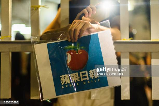Supporter holds a poster of the Apple Daily newspaper logo outside the media company's office building in Hong Kong in the early hours of June 24...