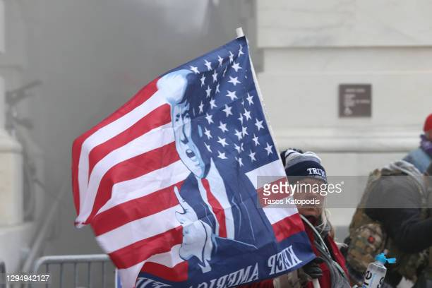 Supporter holds a President Donald Trump flag as protesters gather on the U.S. Capitol Building on January 06, 2021 in Washington, DC. Pro-Trump...