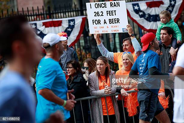A supporter holds a sign as runners make their way north on First Avenue during the 2016 TCS New York City Marathon November 6 2016 in New York City...