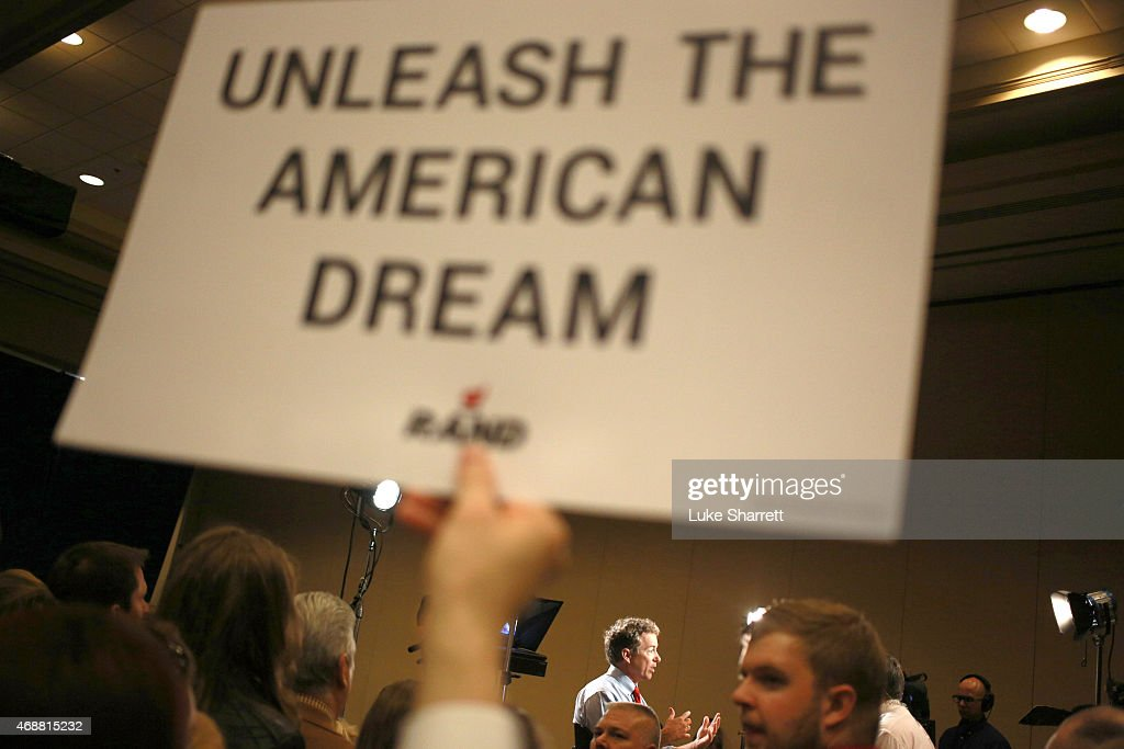 A supporter holds a sign as Sen. Rand Paul (R-KY) sits for an interview with Fox News after announcing his candidacy for the 2016 Republican presidential nomination during an event at the Galt House Hotel on April 7, 2015 in Louisville, Kentucky. Originally an ophthalmologist, Paul rode the Tea Party wave to office in 2010.