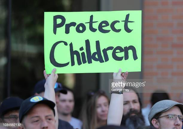 A supporter holds a sign during a rally for Sam Young a former Mormon bishop and founder of Protect the Children as he reads a letter that informed...