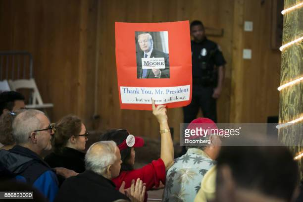 A supporter holds a sign featuring US President Donald Trump ahead of a campaign rally for Roy Moore Republican candidate for US Senate from Alabama...