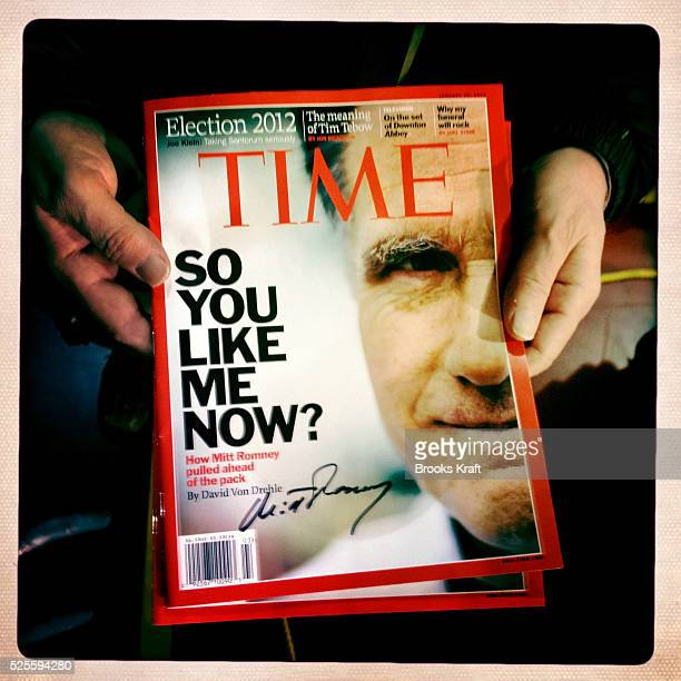 A supporter holds a signed magazine cover of Republican presidential candidate Mitt Romney at a rally in Dover New Hampshire