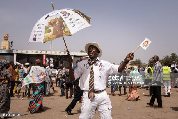 Supporter holds an umbrella and wears a tie bearing portraits of Burkina Faso's ousted president Blaise Compaore during a campaign rally of Burkinabe...
