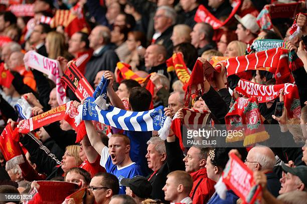 A supporter holds up a blue and white Everton scarf amid Liverpool scarves during a memorial service at Liverpool FC's Anfield football ground in...