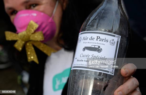 A supporter holds up a bottle of polluted Paris air on March 10 2018 in Paris France Pedestrians and cyclists assembled to support a carfree...