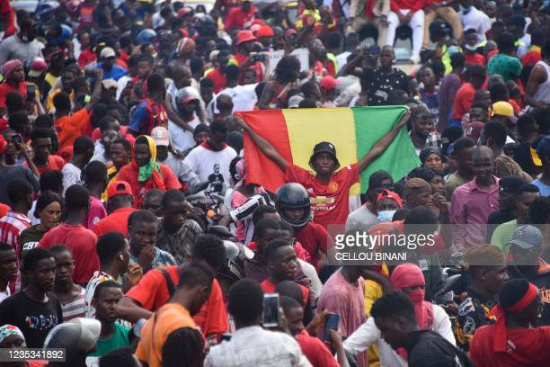 Supporter holds up a Guinean National Flag as exiled activists arrive in Conakry, on September 18, 2021. - Guinea's ruling junta on September 18,...
