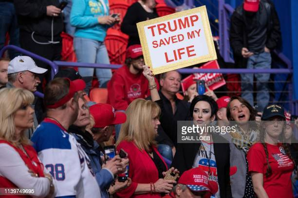 TOPSHOT A supporter holds up a sign as the US president speaks during a Make America Great Again rally in Green Bay Wisconsin April 27 2019