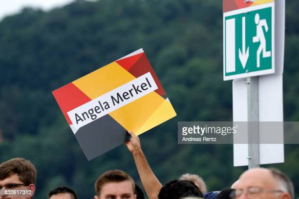 A supporter holds up a sign saying 'Angela Merkel' during an election rally at the headland known as the 'Deutsches Eck' where the Mosel and Rhine...