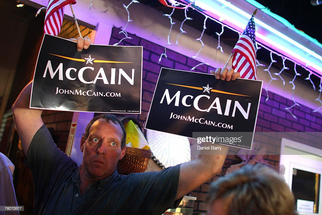 A supporter holds up signs for Republican presidential hopeful and Sen. John McCain (R-AZ) during a campaign stop at the Shell Factory January 26, 2008 in North Ft. Myers, Florida. Republican presidential candidates continue to campaign in Florida for the upcoming primary.