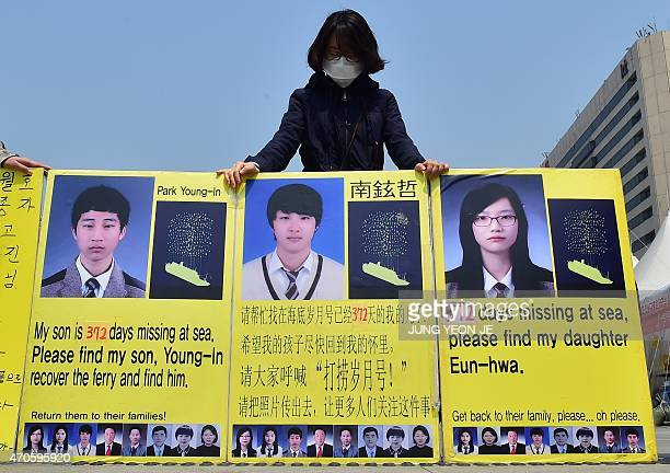 A supporter holds yellow placards showing portraits of missing people from South Korea's Sewol ferry disaster at the Gwanghwamun square where...