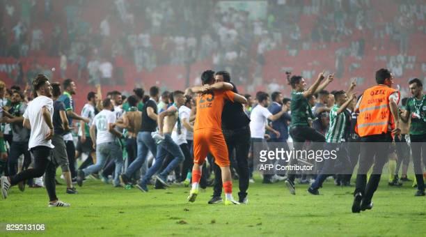 Supporter hugs Konyaspor's goalkeeper Abdulaziz Demircan as football fans invade the pitch during the Turkish Super Cup final football match between...