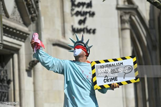 Supporter in a costume of the Statue of Liberty holds a placard in support of Wikileaks founder Julian Assange, outside the Royal Courts of Justice...