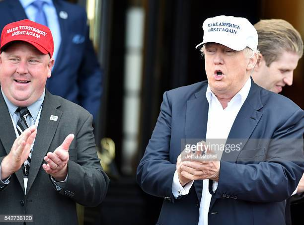 A supporter in a red hat stands next to Presumptive Republican nominee for US president Donald Trump as he arrives to his Trump Turnberry Resort on...