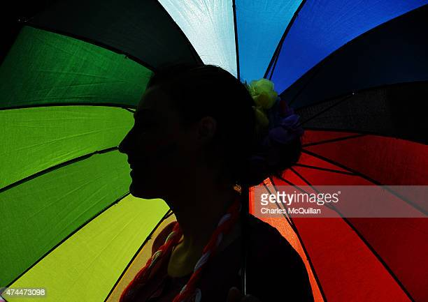 A supporter in favour of samesex marriage stands under a rainbow umbrella as thousands gather in Dublin Castle square awaiting the referendum vote...