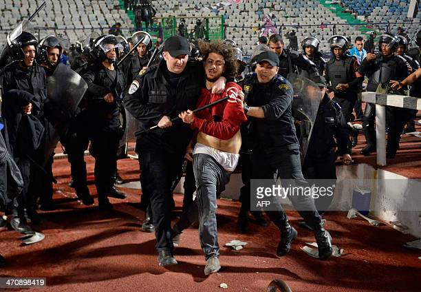 A supporter is arrested by riot policemen during clashes after Egypt's AlAhly won the African Super cup final football match against Tunisia's Club...