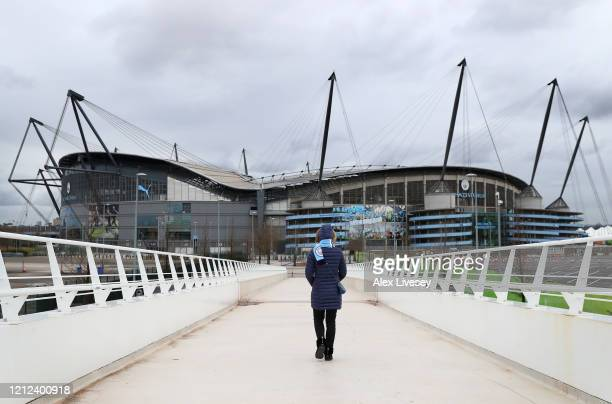 A supporter is seen walking outside the Etihad Stadium home of Manchester City FC as the scheduled match to be played today between Manchester City...