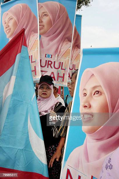 A supporter is surrounded by campaign banners bearing the portrait of Nurul Izzah Anwar daughter of former deputy prime minister and defacto...