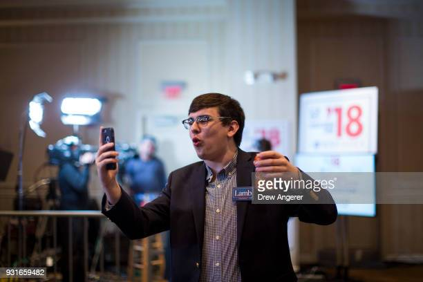 A supporter live streams himself at an election night event for Conor Lamb Democratic congressional candidate for Pennsylvania's 18th district March...