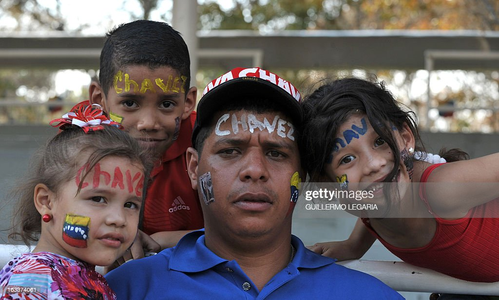 A supporter lwith his children lines up to pay his last respects to late Venezuelan President Hugo Chavez, outside the Military Academy in Caracas on March 8, 2013. Venezuela gave Hugo Chavez a lavish farewell on Friday at a state funeral that brought some of the world's most notorious strongmen to tears, with music, prayers and a fiery speech by his successor. AFP PHOTO/Guillermo Legaria