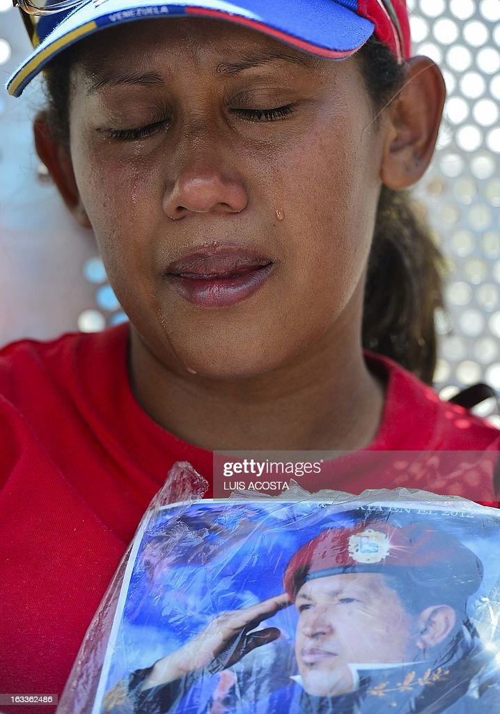 A supporter mourns late Venezuelan President Hugo Chavez during his funeral in Caracas on March 8, 2013. Latin American leaders and US foes paid tribute to Venezuelan leader Hugo Chavez on Friday as he lay in state in a flag-draped coffin during a lavish state funeral before the nation swears-in an interim president. AFP PHOTO/Luis Acosta