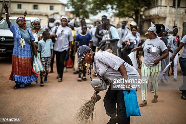 A supporter of Adama Barrow the flagbearer of the coalition of the seven opposition political parties in Gambia sweeps the ground with a broom a...