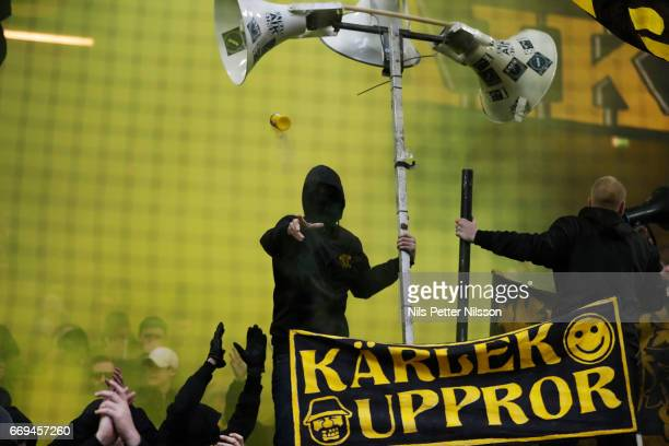 A supporter of AIK throws a smoke grenade during the Allsvenskan match between AIK and Hammarby IF at Friends arena on April 17 2017 in Solna Sweden