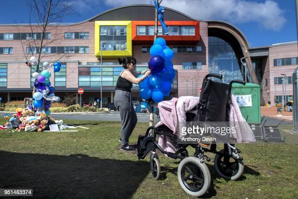 A supporter of Alfie Evans ties baloons to a tree outside Alder Hey Children's Hospital on April 26 2018 in Liverpool England Tom Evans the father of...