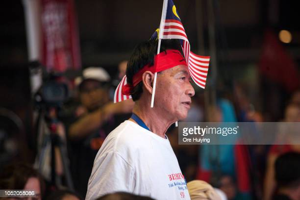 A supporter of Anwar Ibrahim's Pakatan Harapan party waits for the byelection results announcement outside the party's headquarters on October 13...
