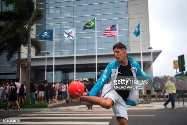 A supporter of Argentina's team Independiente juggles with a football in front of the Hilton Barra hotel in Rio de Janeiro Brazil where the squad is...