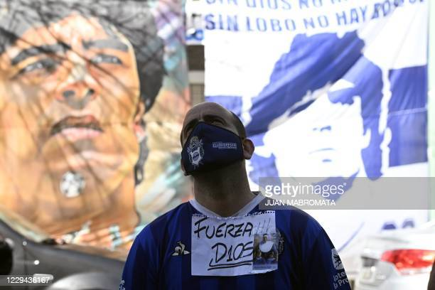 Supporter of Argentine former football star and coach of Gimnasia y Esgrima La Plata stays outside the Ipensa clinic where Maradona has been...