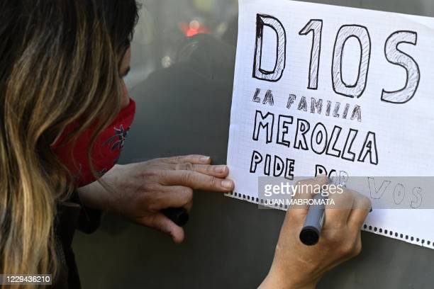 Supporter of Argentine former football star and coach of Gimnasia y Esgrima La Plata Diego Maradona writes a message outside the Ipensa clinic where...
