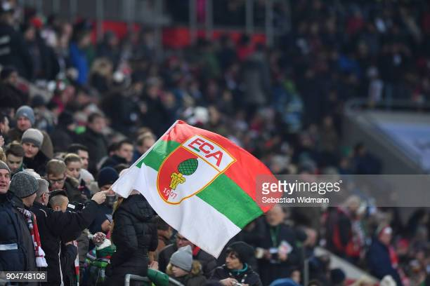 A supporter of Augsburg waves a flag during the Bundesliga match between FC Augsburg and Hamburger SV at WWKArena on January 13 2018 in Augsburg...