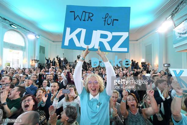 """Supporter of Austria's People's party holding a placard reading """"We for Kurz"""" reacts to exit polls during the party's electoral evening in Vienna,..."""
