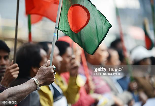 A supporter of Bangladeshi Prime Minister Sheikh Hasina holds a national flag during a rally in front of her political party's headquarters in Dhaka...