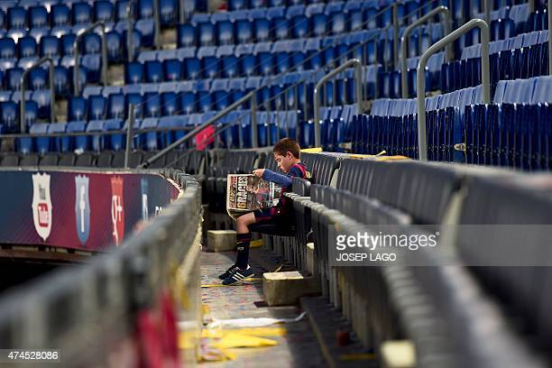 A supporter of Barcelona football club in an empty tribune reads a newspaper with an image of Barcelona's midfielder Xavi Hernandez on the front...
