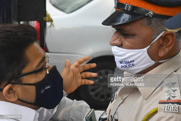 A supporter of Bharatiya Janata Party is stopped by a policeman while protesting against the arrest of Indian television journalist Arnab Goswami in...