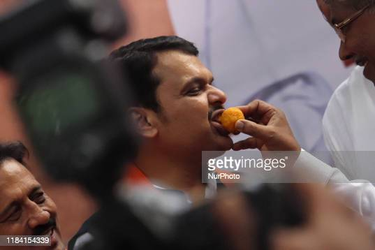 Supporter of Bharatiya Janata Party offers sweets to Maharashtra chief minister Devendra Fadnavis during celebrations after being sworn-in as...