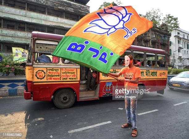 Supporter of Bharatiya Janata Party seen wearing a Mask of Narendra Modi while weaving BJP Flags in front of the Party Head quarter in Kolkata after...