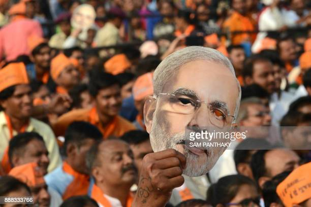 A supporter of Bhartiya Janta Party hold a cut out of Indian Prime Minister Narendra Modi during a rally at Kalol some 30 kms from Ahmedabad on...